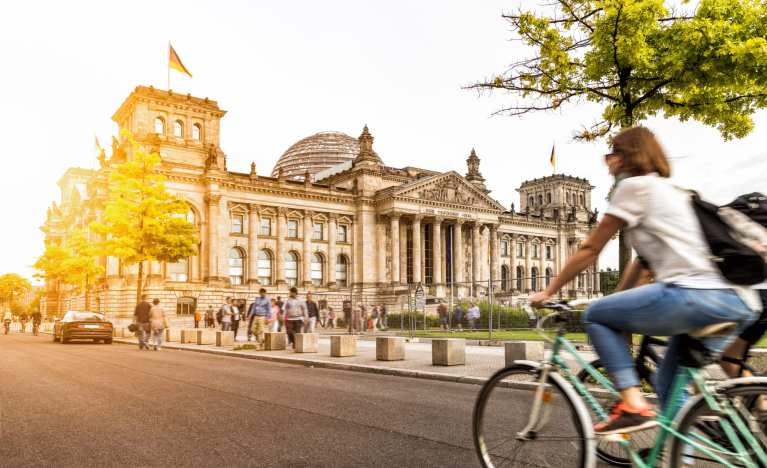 A local Berlin woman bikes past the famous Reichstag building   © Shutterstock