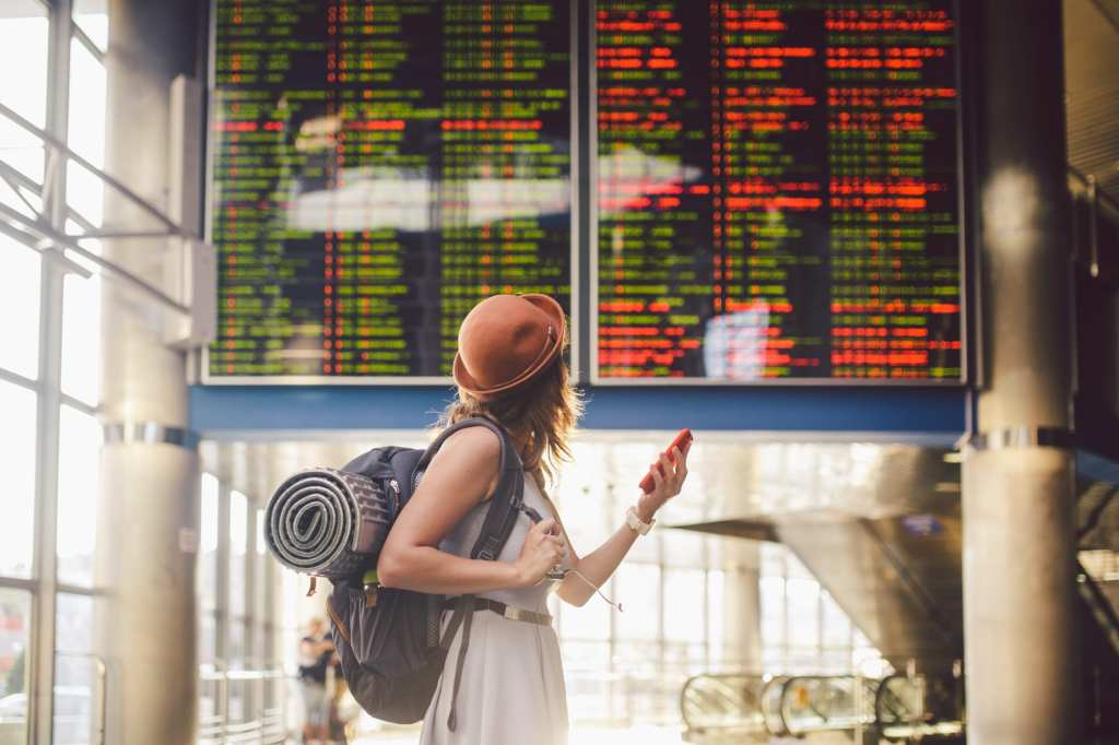 A solo female traveler looks at departure times at the airport | © Fotoliza/Shutterstock