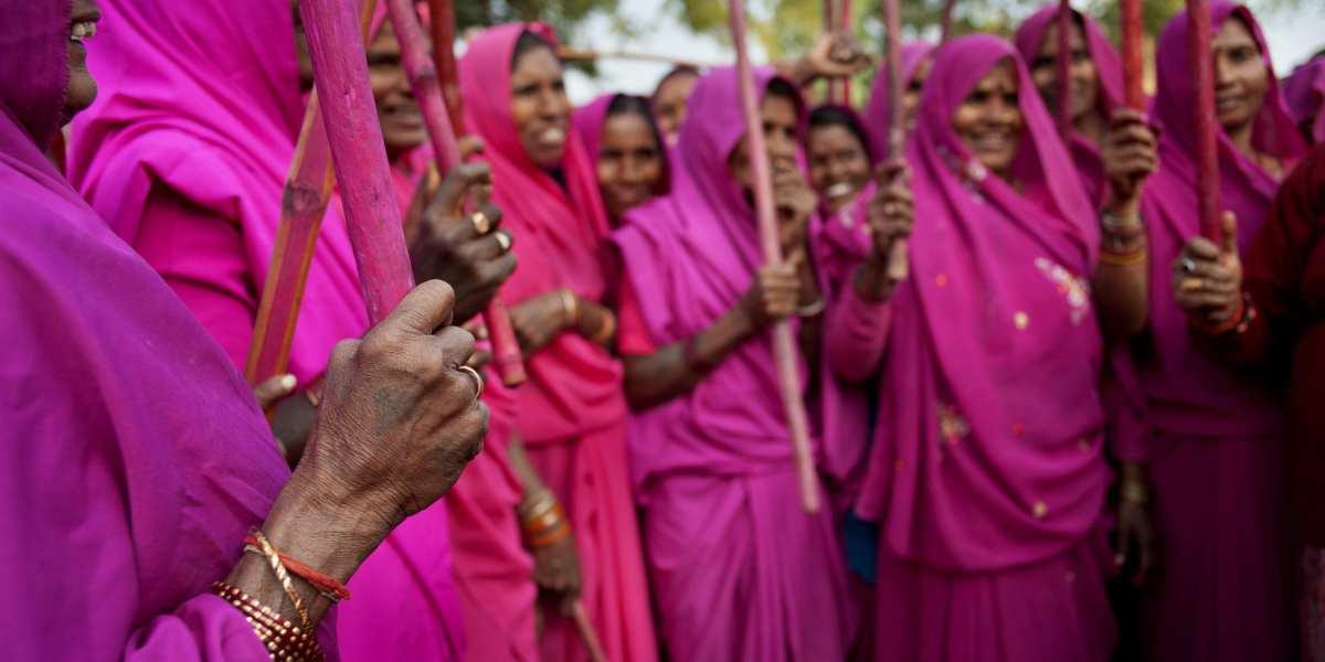 Gulabi Gang in pink saris, yielding their sticks | © Jonas Gratzer/LightRocket via Getty