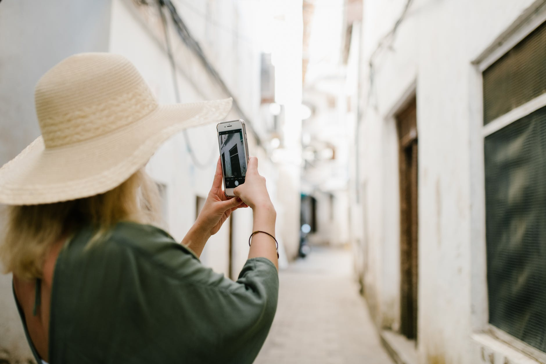woman taking photo of building in alley
