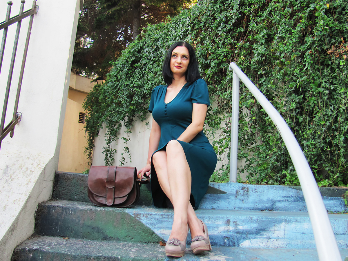 Woman sitting wearing green dress brown bag