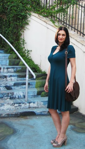 Brunette young woman wearing green dress brown bag