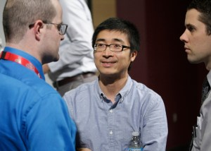 Panelist and UNMC researcher Bin Duan, Ph.D., meets with guests immediately after the event.