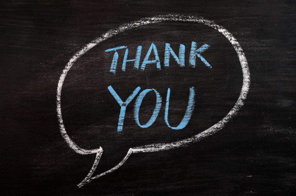 Thank you written in a speech bubble with blue chalk on a smudged blackboard