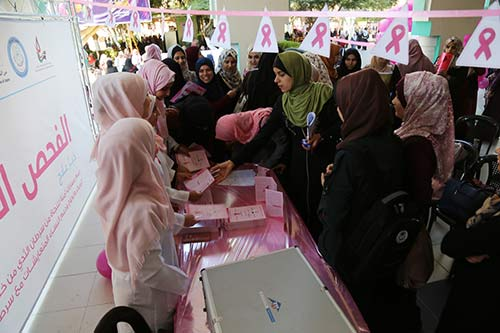Women in pink hijabs speak to women fathering around a table with a pink tablecloth.