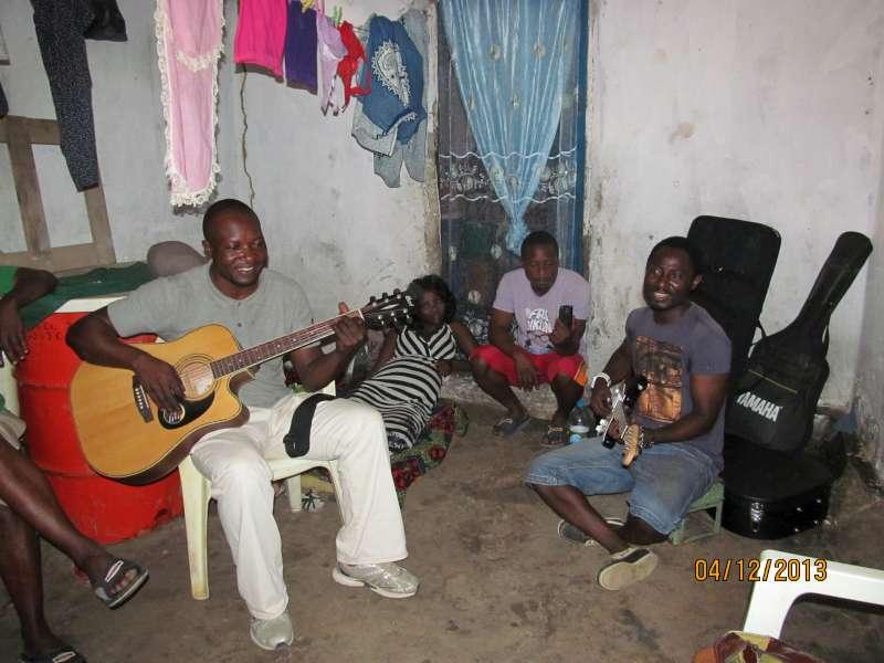 Freeboy Gbaryeel (à esquerda) toca em Luanda, atraindo vizinhos amantes de música. Foto: ACNUR/Tina Ghelli