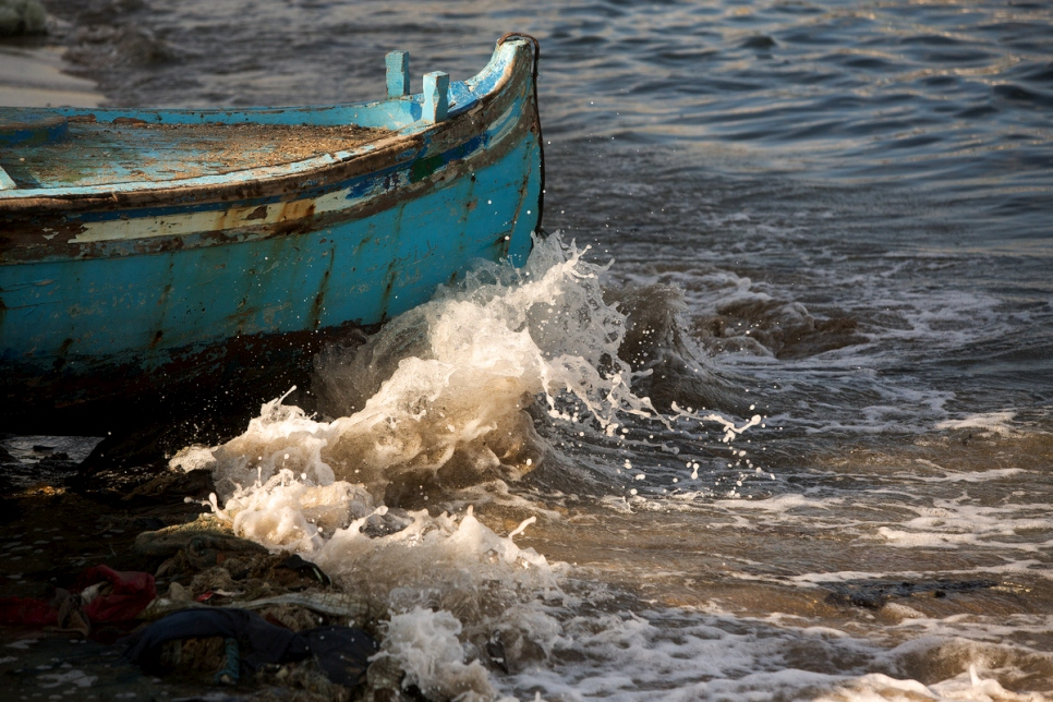 Waves crash against the bow of a teal fishing boat