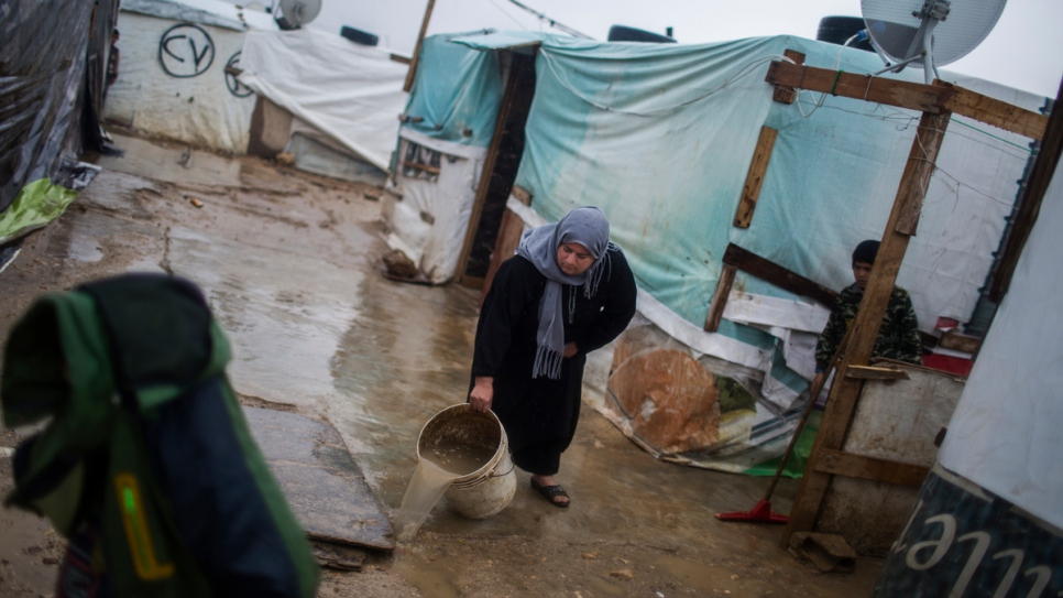 Syrian refugee Fatima sluices sewage away from her temporary home at an informal settlement on the outskirts of Zahle in the Bekaa Valley.