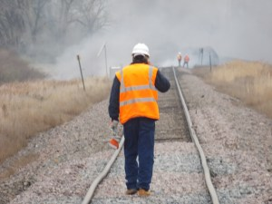 A BNSF maintenance worker stops to talk on his cell phone while inspecting the tracks just east of the accident site. Just ahead of him is the end of the stretch where the track has beeen raised.