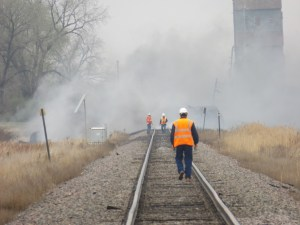 The Heimdal elevator is visible just behind the site of today's accident as a BNSF maintenance worker walks toward two other BNSF employees.