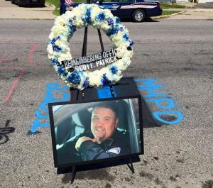 A memorial wreath and an enlarged photo of Scott Patrick, a Mendota Heights (Minn.) police officer killed on duty July 30, 2014, is displayed at the site of Patrick's death during a ceremony to dedicate the Office Scott Patrick Memorial Highway in West St. Paul and Mendota Heights July 30, 2015. The photo of Patrick was taken in 2013 by one of his brothers, Mike Brue. Highway dedication photo by Christopher Paul Madson Patrick.