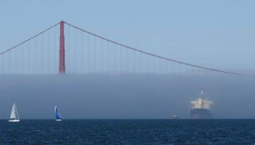 Big ship and tug emerging from fog after passing under Golden Gate Bridge, seen from San Francisco Maritime National Historical Park.