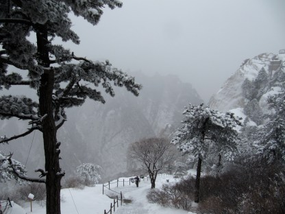 A lone porter walks along a trail on a snowy day in Mount Hua in western China.