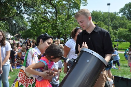 Nick Skuza, fourth-year Astro Physics major at the University of Minnesota, and Bell Museum educational assistant, guided visitors to view the eclipse through a telescope.