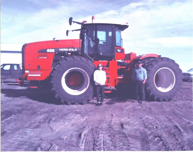 Aunt Deloris and my cousin, Jimmy, with her new red Versatile tractor. Neighbors say Uncle Leonard, a John Deere man, is rolling over in his grave.