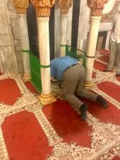A man kneels to pray at the mosque at the site of Abraham's tomb.