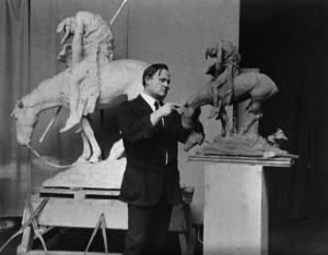 """James Earle Fraser in his studio with a clay model of the """"The End of the Trail"""" sculpture, ca. 1910. (Special Collections Research Center, Syracuse University Libraries, N.Y.)"""