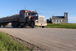 A tanker passes through a ghost town east of Williston, N.D. Drilling a new well requires more than 2,000 truck trips, putting a strain on rural North Dakota's system of unpaved roads.