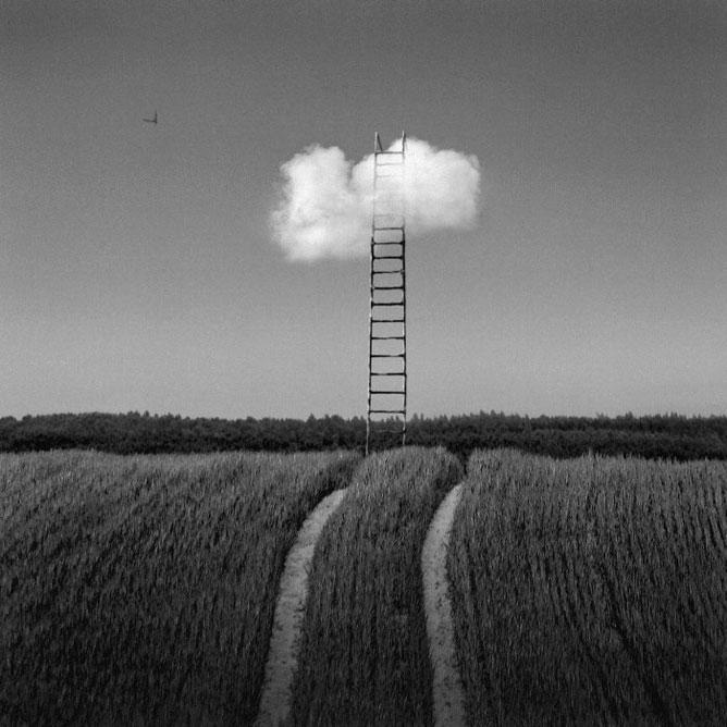 Fekete fehér kép, mezőn álló létra eléri az égen lebegő felhőt
