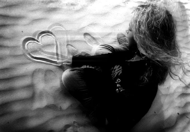 Szívet a tengerparti homokba rajzoló kislány, fekete fehér művészi kép