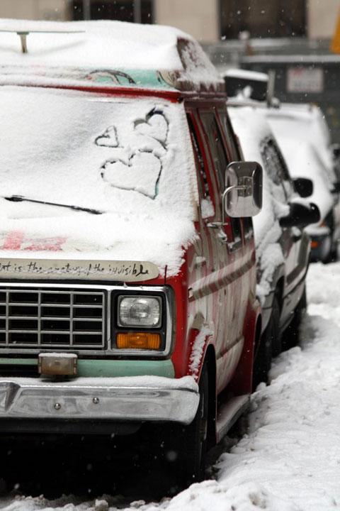 Hóval ellepett autók az utcán szivekkel a szélvédőre rajzolva.