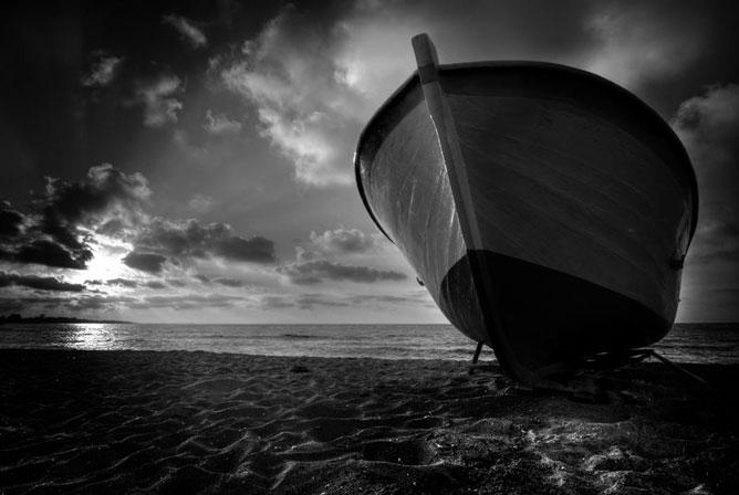 Partra ért csónak; túlpartra jutott; felhők mögül a nap; fekete-fehér fotó.