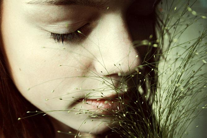 Behunyt szemű lány szagolja a virágot