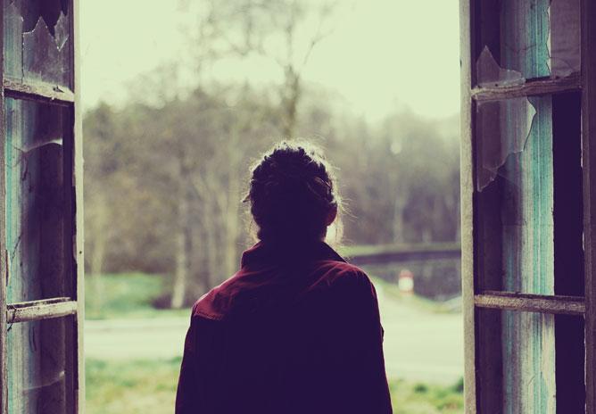 Egy lány kinéz a törött üvegű nyitott ablakon a kertre, a természetre, merengve.
