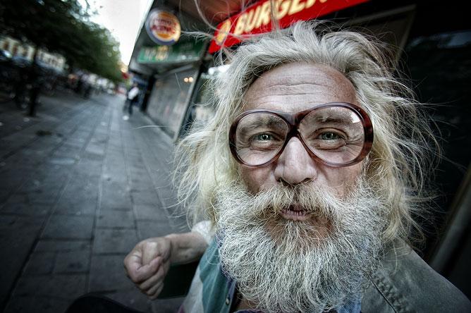 Hajléktalan szemüveges ember érdeklődő tekintettel.