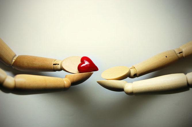 Kis fakezek egy kicsi piros szívet adnak egymásnak.