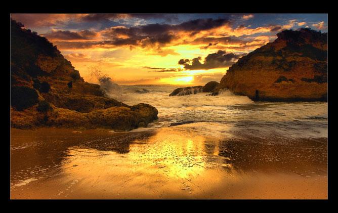 Gyönyörű naplemente a sziklás parton.