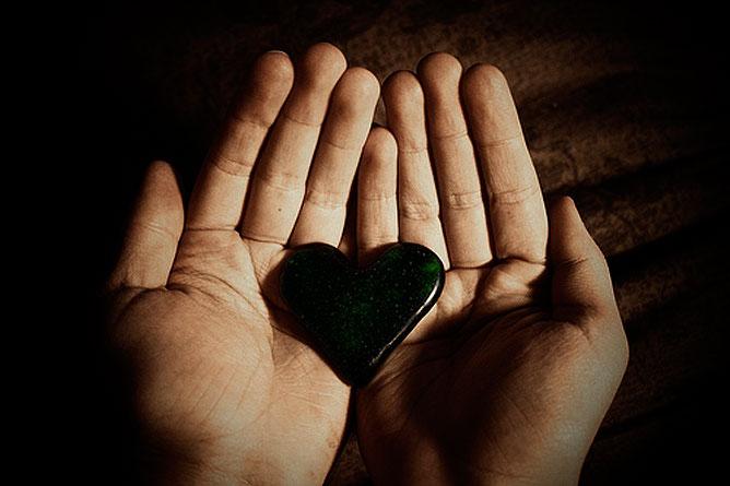 Egy szív kő egy emberi tenyérben.