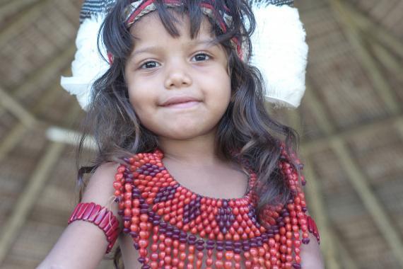 Menina indígena olha para a câmera. Ela está com uma roupa de miçangas.