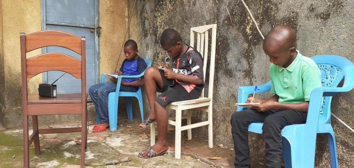 Des jeunes garçons prenant notes des cours qu'ils sont en train de suivre à la Radio