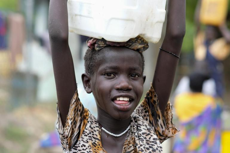 Sandy Chuol, 10, heads home with the jerrycan of clean water