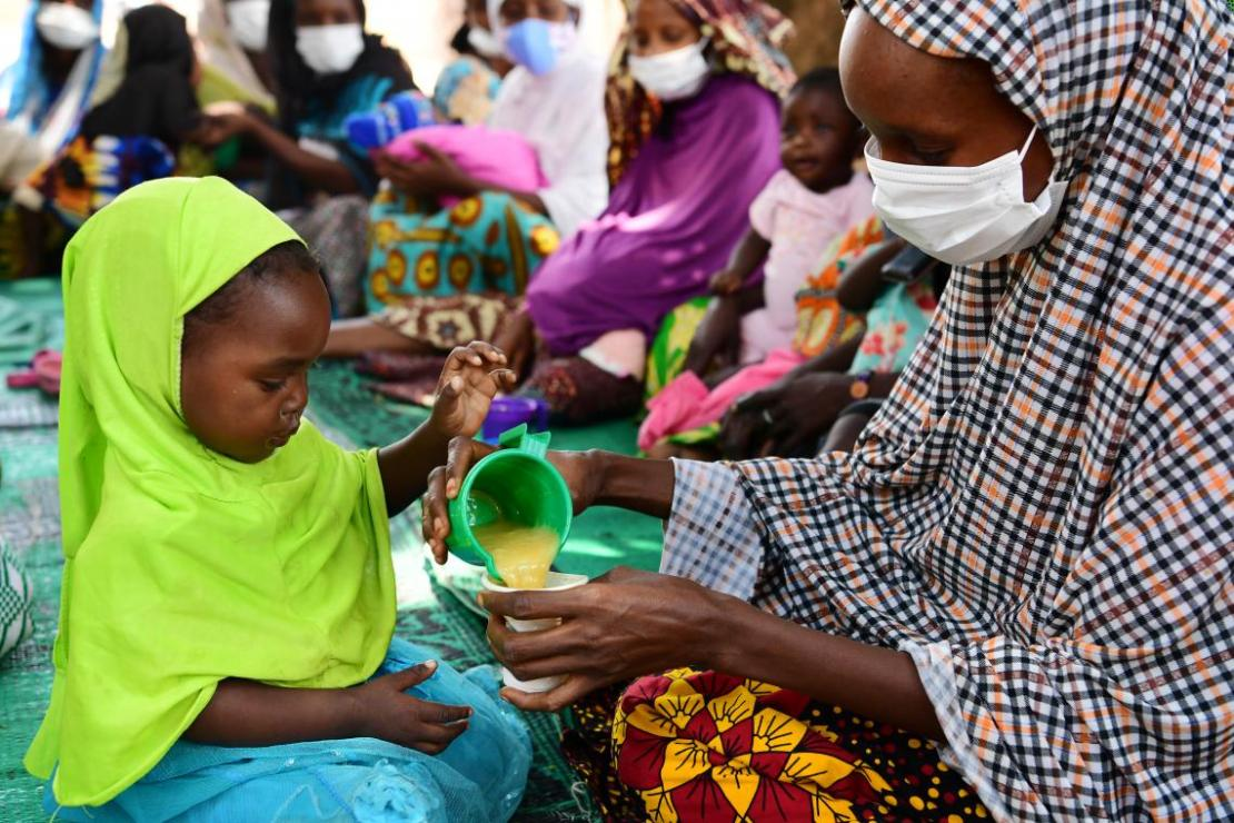 Varias madres y sus bebés participan en una actividad de nutrición en su comunidad, en Bertoua, Camerún.