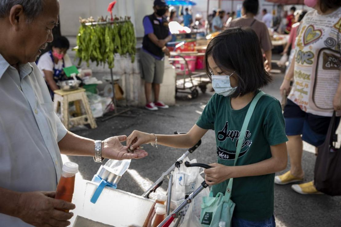 Una niña vende botellas del jugo que prepara su abuela en un mercado de Tailandia.