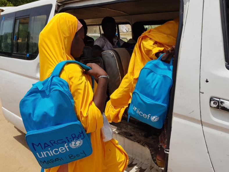 Girls wearing UNICEF backpacks climb into a van, Nigeria
