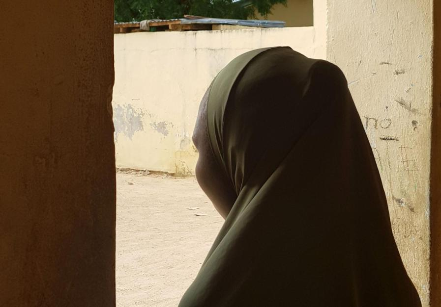 A girl looks out a window, Nigeria