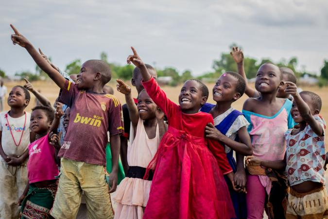 Children look on excited at the testing of unmanned aerial vehicle (UAVs) or drones in Malawi.
