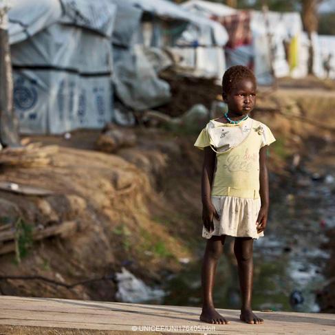 Una niña está parada en un puente sobre un canal de drenaje en Sudán del Sur