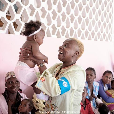 La Embajadora de UNICEF Angelique Kidjo sostiene un bebé en un centro de salud en Mozambique