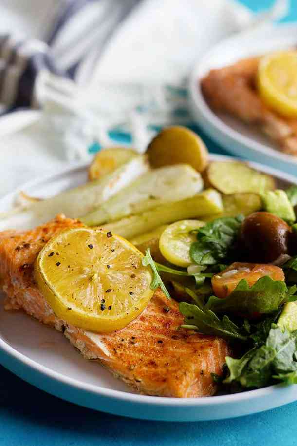Tender and flavorful baked salmon fillet with lemon served with a delicious arugula avocado salad. This baked salmon fillet recipe is baked in a sheet pan.