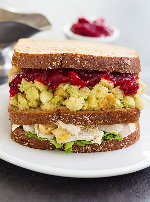 A Thanksgiving sandwich is made of several layers of leftover Thanksgiving food such as turkey, stuffing and cranberry sauce.