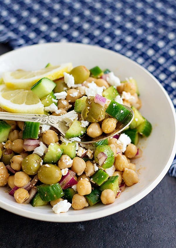 Greek chickpea salad is made with olives, chickpeas, onions, feta and cucumbers.
