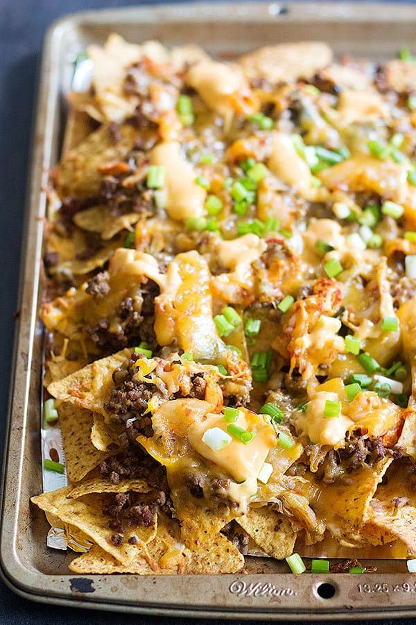 Korean Beef Nachos are a new twist on traditional nachos. The delicious Korean beef topped with Mexican blend cheese and served with sriracha mayo is an unbeatable combination!