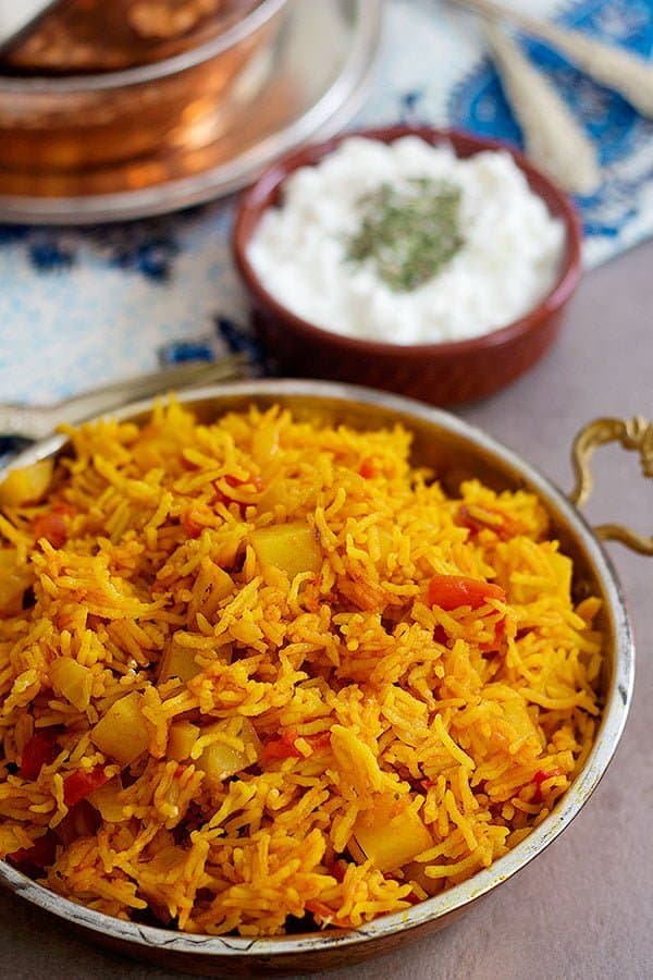 Tomato rice made with potatoes and served with salad shirazi and yogurt topped with dried mint.