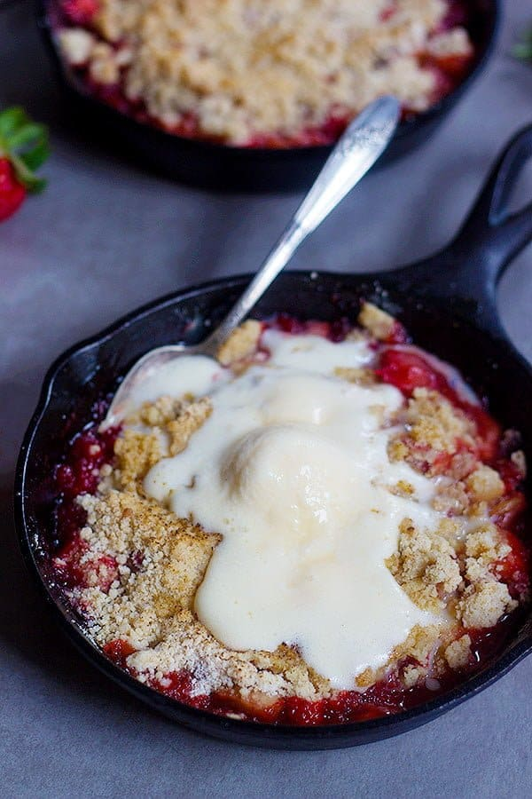 Strawberry Rhubarb Crumble served with vanilla ice cream in a small cast iron skillet.
