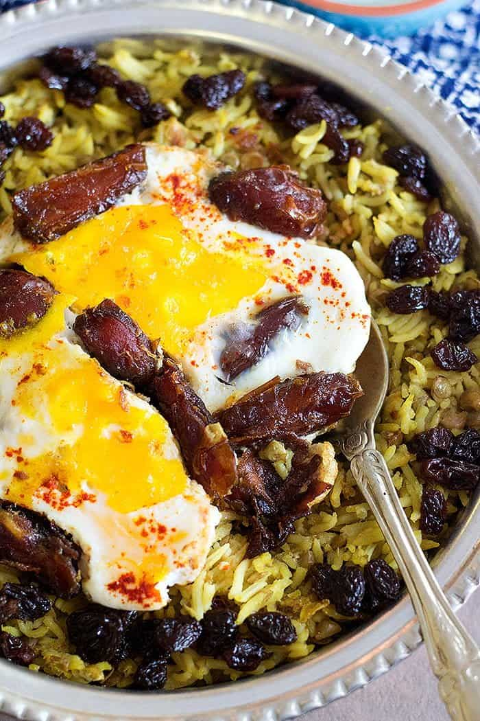 Spice up your meatless Monday with this Vegetarian Persian Lentil Rice. Rice cooked with lentils and topped with eggs and dates, it's good!