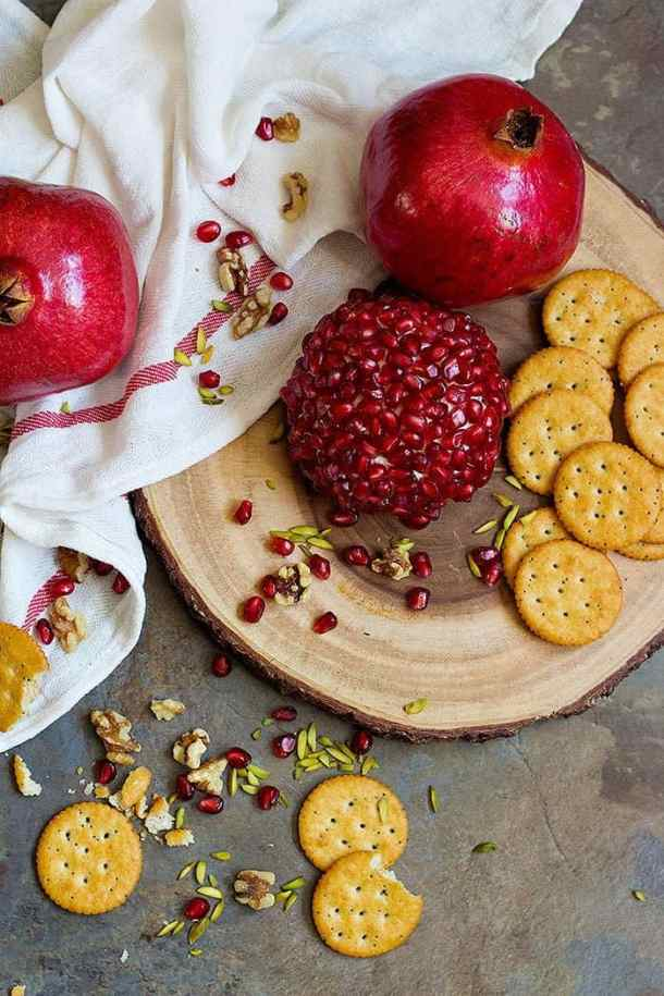 Pomegranate Cheese Ball with pomegranate arils, pistachios and crackers.